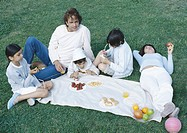 Parents with boys and girl having picnic on lawn