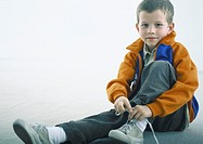 Boy sitting on floor, tying shoe