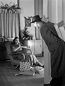 A photograph of a man at the door to a living room bringing Christmas presents home for a young woman, taken by Photographic Advertising Limited in ab...