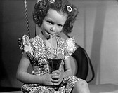 A photograph of a smilling little girl drinking juice through a straw, taken by Photographic Advertising Limited in 1950.  Photographic Advertising Li...
