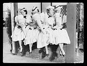 A photograph of four women in milkmaid costumes pretending to eat giant ice cream cones, taken by Tomlin for the Daily Herald newspaper on 29 January,...