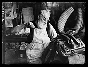 A photograph of a saddler at work, taken by Esten for the Daily Herald newspaper on 18 November, 1943.   Mr Frederick Ewens repairs a horse harness in...