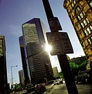 Low angle view of traffic sign silhouetted by sunbeams in urban setting (thumbnail)