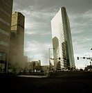 Low angle view of futuristic building and steam in urban setting against cloudy sky (thumbnail)