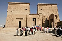 Tourists visiting Philae temple, built for Isis. On the first pylon are pictures of Isis and Horus. Aswan. Egypt