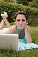 Woman lying in grass with laptop, portrait