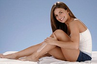 Woman spreading moisturizer on her legs, portrait