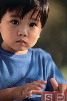 Asian boy playing with blocks, portrait