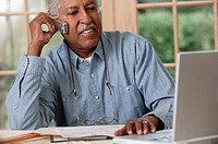 Man with laptop talking on telephone