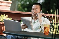 Man with laptop talking on cell phone