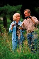 Couple hiking, both holding binoculars