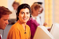 Woman with telephone headset on at computer