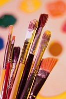 Paintbrushes with canvas and colors in background