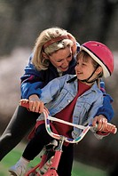 Girl riding Bicycle with Mother´s help