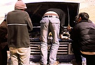 Four people standing around an opened hood of a 4WD jeep, one standing on the bumper with behind to camera attempting to fix the problem. Rural Tibet,...