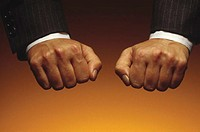 Businessman holding two fists as if hiding something in one.