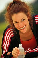 Woman dressed in fitness attire, holding bottled water, portrait