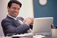 Businessman sitting at desk with laptop, portrait