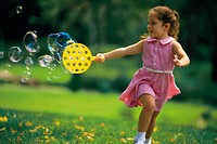 Little girl running with bubble toy