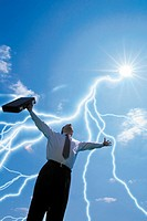 Composite of low angle view of businessman with arms raised toward sky, with sun and lightning bolts