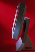 Side view of a flat screen computer monitor with a red background