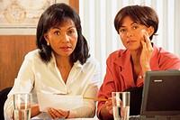Two businesswomen at desk, portrait