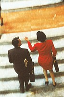 Businesspeople climbing stairs and talking, blurred