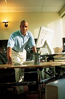 Man standing behind computer desk, portrait.