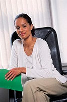 Woman sitting in office chair, holding folder, portrait
