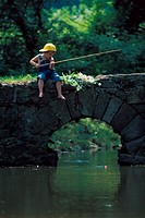 Boy fishing off bridge