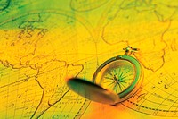 Compass on world map, green and yellow color tones