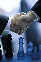 Businessmen shaking hands over chessboard