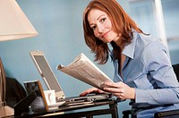 Woman working with laptop and holding financial pages of newspaper, portrait