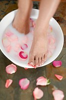 Woman´s feet in water with rose petals