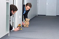 Businessmen playing with teddy bears