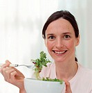 Smiling woman eating salad