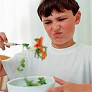 Boy looking disgusted at salad (thumbnail)