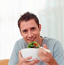 Man eating a bowl of salad