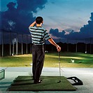 Man practising on driving range (thumbnail)