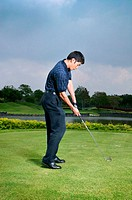 Asian man playing golf
