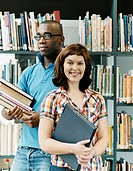 Portrait of Two Mature Students Standing in a Library Holding Books