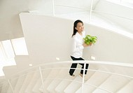 Blurred Motion Shot of a Woman Ascending a White Stairway Carrying a Potted Plant