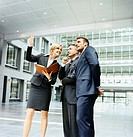 Businesswoman Holding a Folder Shows Two Businessmen Around a Large Lobby in a Modern Building