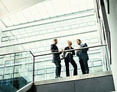 Three Business Colleagues Stand at the Top of a Staircase in a Modern Building Having a Coffee Break