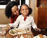 Mother and Daughter Sit at a Dining Table Eating a Plate of Food