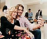 Couple Sits on Sofa Photographing Themselves With a Mobile Phone, Four People in the Background