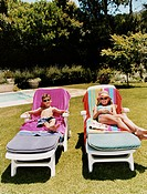 Brother and Sister Lie on Deck Chairs Sunbathing