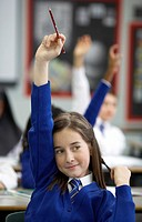 Schoolgirl With Her Hand Raised in a Classroom