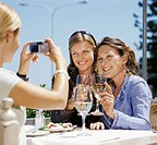 Women Sit at a Restaurant Table for Lunch, Their Friend Taking a Picture of Them Whilst They Make a Toast