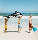 Boys Carrying an Animal Inflatable Following Their Father Carrying Swimming Flippers on a Beach